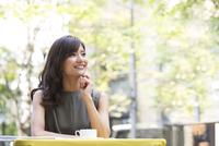 オープンカフェで遠くを眺める女性