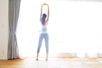 窓際で背伸びをする女性