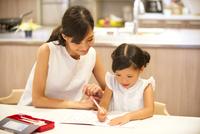 子供の勉強を見る母親