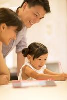 子供の勉強を見る母親と父親