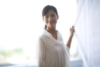 カーテンの傍で微笑む女性