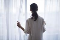 窓の外を見つめる女性の後ろ姿