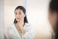 鏡の前で肌のチェックをする女性