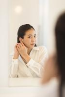 鏡の前でピアスを身につける女性