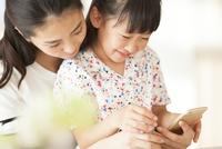 スマートフォンを見て楽しむ親子 33000004052| 写真素材・ストックフォト・画像・イラスト素材|アマナイメージズ