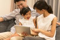 ソファーでタブレットPCを見る家族 33000004066| 写真素材・ストックフォト・画像・イラスト素材|アマナイメージズ