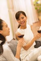 ソファーに座ってワインを手に笑い合う女性2人