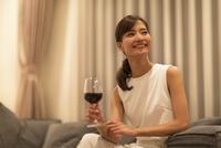 ソファーに座ってワインを手に遠くを眺める女性