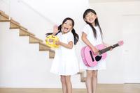 タンバリンを叩く女の子とギターを弾く女の子