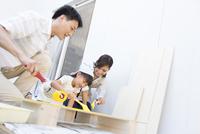 ベニヤ板にペンキを塗る家族