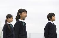 屋上に立って遠くを眺める小学生たち