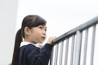 屋上から遠くを眺める小学生の女の子