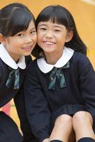 体育館で座って微笑む小学生の女の子2人