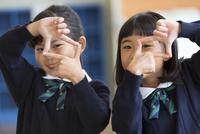 指でカメラのポーズをとる小学生の女の子2人 33000004154| 写真素材・ストックフォト・画像・イラスト素材|アマナイメージズ