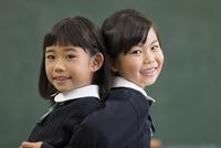 黒板の前で背中を合わせる小学生の女の子3人