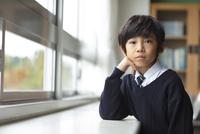 教室の窓際で肘をついて座る小学生の男の子