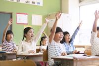 授業中に手を上げる小学生たち