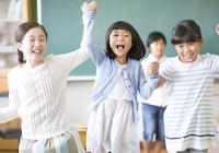 黒板の前で手を取り合って喜ぶ女の子たち