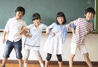 黒板の前で腕を組んで笑う子供たち