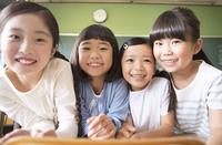 教室で肩を並べて笑う女の子4人