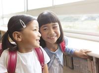 教室でランドセルを背負って笑う女の子2人 33000004238  写真素材・ストックフォト・画像・イラスト素材 アマナイメージズ