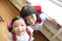教室でランドセルを背負って笑う女の子2人
