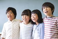 黒板の前で肩を組んで笑う子供たち