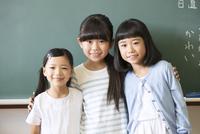 黒板の前で肩を組んで笑う女の子3人