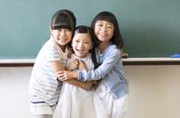 黒板の前で寄り添って笑う女の子3人
