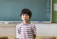 黒板の前に立つ男の子