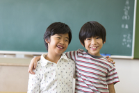 黒板の前で肩を組んで笑う男の子2人 33000004251| 写真素材・ストックフォト・画像・イラスト素材|アマナイメージズ