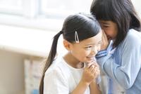 教室で内緒話をする女の子2人