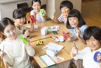 色を塗った作品を見せる子供たち