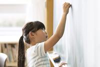 黒板に文字を書こうとする女の子 33000004319| 写真素材・ストックフォト・画像・イラスト素材|アマナイメージズ