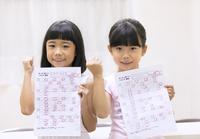 テストの結果に喜ぶ女の子2人 33000004329| 写真素材・ストックフォト・画像・イラスト素材|アマナイメージズ