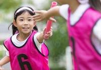 リレーのバトンを渡す女の子 33000004336| 写真素材・ストックフォト・画像・イラスト素材|アマナイメージズ