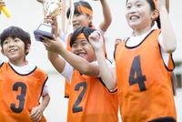 優勝カップを持って喜ぶ子供たち 33000004343| 写真素材・ストックフォト・画像・イラスト素材|アマナイメージズ
