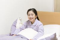 ベッドの上で微笑む女の子 33000004353| 写真素材・ストックフォト・画像・イラスト素材|アマナイメージズ