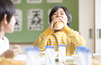 給食のパンを口に頬張る男の子 33000004359| 写真素材・ストックフォト・画像・イラスト素材|アマナイメージズ