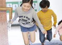 学校の階段を駆ける女の子と男の子 33000004363| 写真素材・ストックフォト・画像・イラスト素材|アマナイメージズ