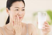 牛乳を手に微笑む女性 33000004407| 写真素材・ストックフォト・画像・イラスト素材|アマナイメージズ