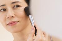 チークブラシを顔にあてる女性 33000004454| 写真素材・ストックフォト・画像・イラスト素材|アマナイメージズ