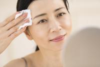 頬にコットンをあてスキンケアをする女性 33000004464| 写真素材・ストックフォト・画像・イラスト素材|アマナイメージズ