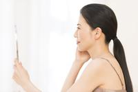 手鏡を見る女性の横顔