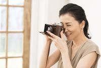 カメラで写真を撮っている女性 33000004607| 写真素材・ストックフォト・画像・イラスト素材|アマナイメージズ