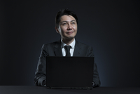 ノートPCの前で上を見上げるビジネス男性 33000004683| 写真素材・ストックフォト・画像・イラスト素材|アマナイメージズ