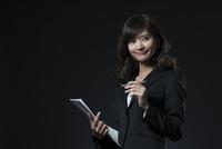 資料とペンを手に持ち微笑むビジネス女性 33000004698| 写真素材・ストックフォト・画像・イラスト素材|アマナイメージズ