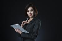 資料とペンを手に持つビジネス女性 33000004713| 写真素材・ストックフォト・画像・イラスト素材|アマナイメージズ