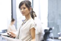 スマホを持ち横を向くビジネス女性 33000004772| 写真素材・ストックフォト・画像・イラスト素材|アマナイメージズ