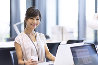 PCの前でスマホを持つビジネス女性 33000004785| 写真素材・ストックフォト・画像・イラスト素材|アマナイメージズ